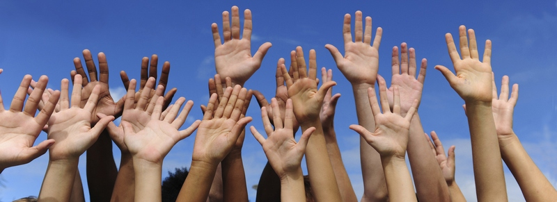 Multiethnic raised hands and writing volunteer