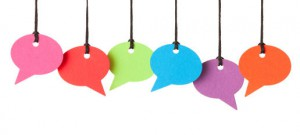 Six blank speech bubbles hanging from thread