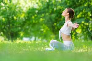 Profile of woman sitting in lotus position with outstretched arms. Concept of healthy lifestyle and relaxation